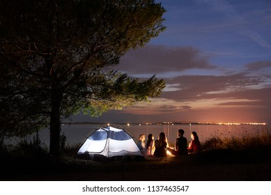 Group of five travellers, girls and boy having a rest on lake shore under tree around campfire at tourist tent on quiet water surface and blue evening sky background. Tourism and camping concept.