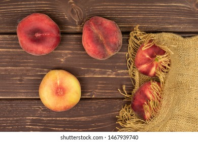 Group of five whole fresh red peach prunus persica platycarpa on natural sackcloth flatlay on brown wood
