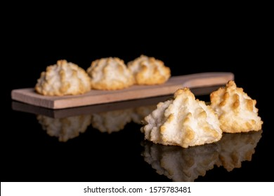 Group of five whole homemade golden coconut biscuit on small wooden cutting board isolated on black glass