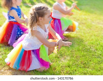 Group of five years old girls dancing during a preschool performance outdoor while a sunny day