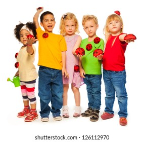 Group of five years old kids with bright watering can and beetles