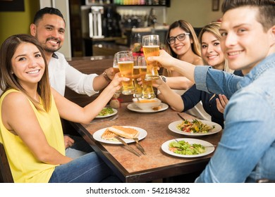 Group of five young adults eating dinner in a restaurant and making a toast with beer. Focus on beer