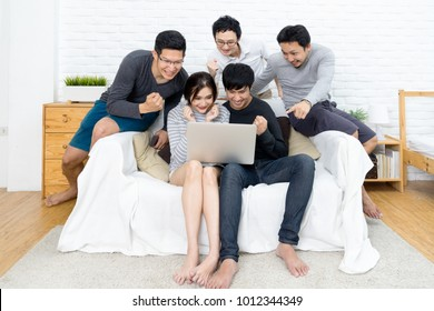 Group of five young asian people watching something with laptop and celebrate together at sofa in home or room. Happy and cheerful with friends in casual style. Funny and cheerful activity concept.