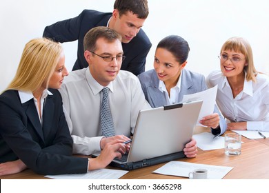 Group of five young businesspeople gathered together around the laptop discussing interesting question