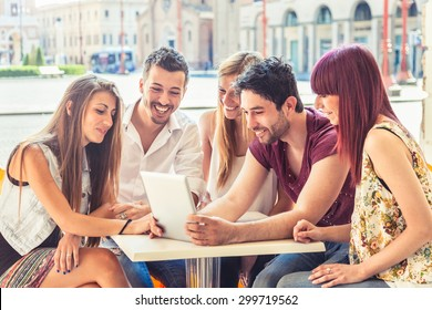 A group of five young friends (two men and three women) looking at a tablet sitting together at a table in a bar in the arcades in a hot summer day
