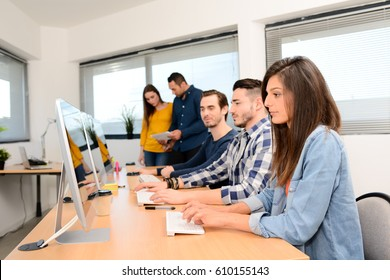 group of five young people student with teacher in computer school classroom learning programming with desktop computer in a row