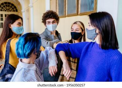 Eine Gruppe von fünf Jugendlichen, die Gesichtsmasken tragen und dabei ihre Ellenbogen stoßen, anstatt sich in einem Universitätsgebäude zu grüßen. Neues Konzept der sozialen Regeln. Die Schüler treffen sich zusammen.