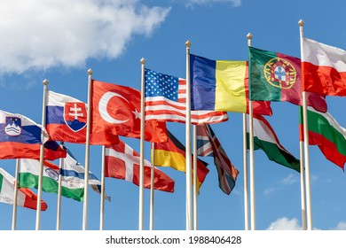 Group of flags of various states - as a symbol of world cooperation. Flags of the countries of the world on flagpoles flutter in the wind against the background of a blue sky