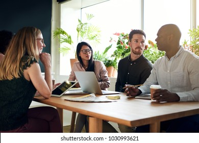 Group of focused designers having a meeting together while sitting around a table in the boardroom of a modern office