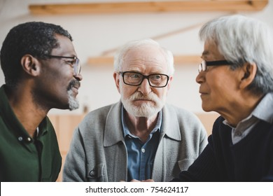 group of focused multiethnic senior friends playing staring contest