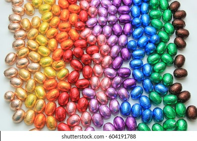 a group of foil wrapped chocolate easter eggs in rainbow colors