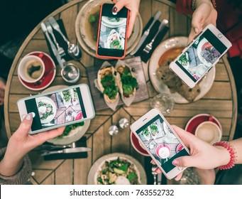 Grupo de bloggers de comida tomando fotos de los platos en la mesa del restaurante. Vista superior. Almuerzo de amigos, fondos de medios sociales