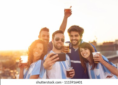 Group of football fans drinking beer and having fun before the game, taking a selfie on a building rooftop terrace. Focus on the girls