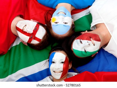 Group of football fans with painted faces lying over the South African flag