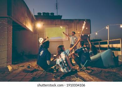 Gruppe von Fußballfans, die auf einer Dachterrasse im Gebäude ein Spiel gucken, nach dem Tor jubeln und mit Sparklern schwingen