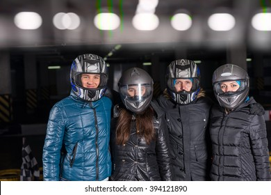 Group of four adult bumper car racing amateurs in thick winter coats and helmets