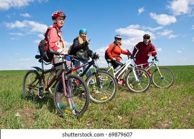 A group of four adults on bicycles in the countryside. Everyone can ride a bike. Everyone who rides a bike is my friend.