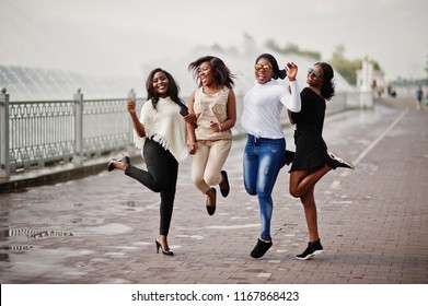 Group of four african american girls having fun and jumping against lake with fountains.