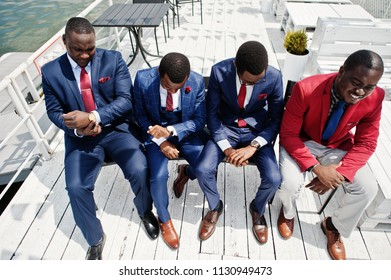 Group of four african american happy succesfull mans at suit. Rich black business mans sitting at chairs and looking at watches. Business time concept.