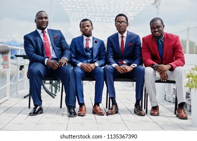 Group of four african american happy succesfull mans at suit. Rich black business mans sitting at chairs.