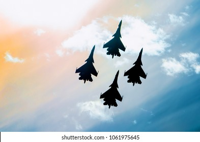 Group of four aircraft fighter jet airplane sun glow toned sky