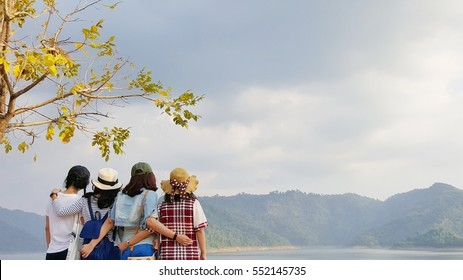 Group of four Asian girls standing back and looking at beautiful mountain landscape. Best friends concept