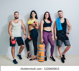 Group of four athletic young friends standing together in gym on the grey wall after a difficult workout session. Fitness concept.