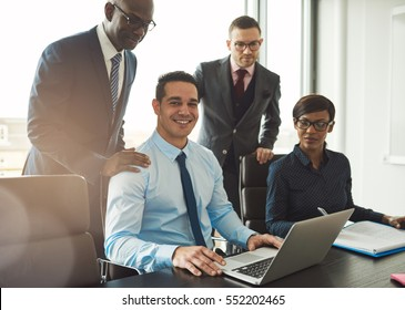 Group of four Black, Hispanic and Caucasian young business people in a meeting at their office in front of large window