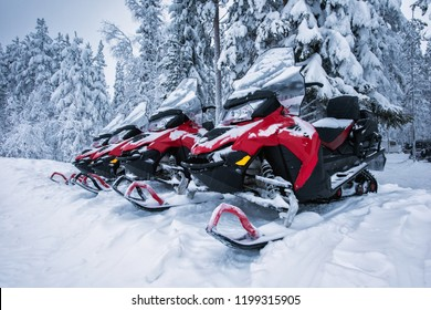 Group of four brightly colored red and black snowmobiles are ready for adventure ride. Vehicles parked in line near beautiful forest in Lapland, Finland. Heavy snow. Winter seasonal landscape.