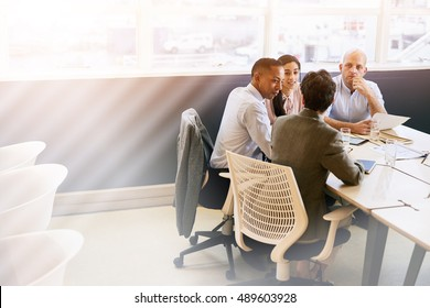 A group of four business executives conducting a meeting in a modern office space with bright copy space to the left of them.