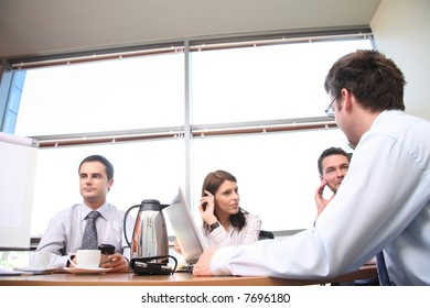 A group of four business people gather around a conference room table for a working discussion to plan a new project.