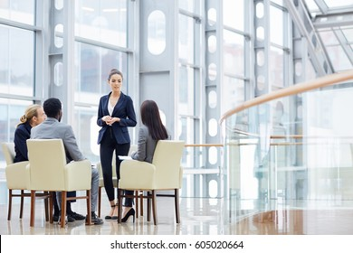 Group of four business people sitting in armchairs during meeting, one woman giving presentation in glass hall of modern office building