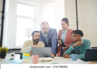 Groupe de quatre hommes d'affaires travaillant ensemble sur un nouveau projet, étudiant les statistiques sur l'ordinateur portable, photo horizontale