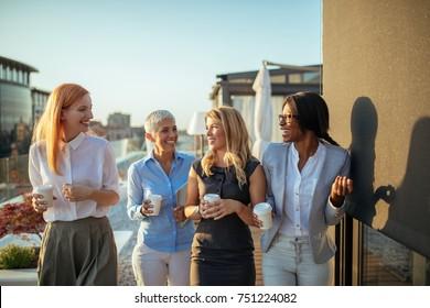 Group of four businesswomen talking