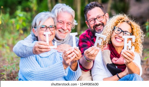 Group of four caucasian people family together with life blocks posing happy and cheerful -defocused backgroud of outdoor nature forest - save planet and enjoy lifestyle concept - focus on blocks