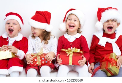 Group of four children in Christmas hat with presents