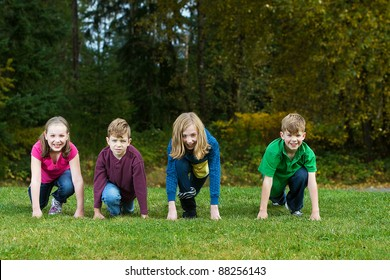 A group of four children lined up ready to race in a park.