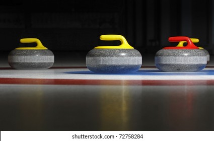 Group of four curling stones in the rings with dark background and ice reflection.