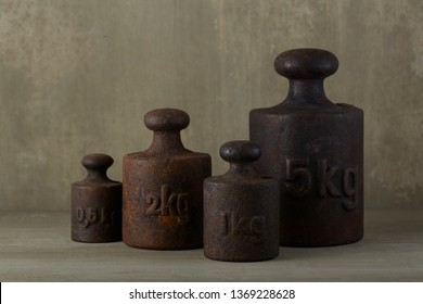 group of four different sized vintage metal scale weights standing next to each other on concrete-like backround.