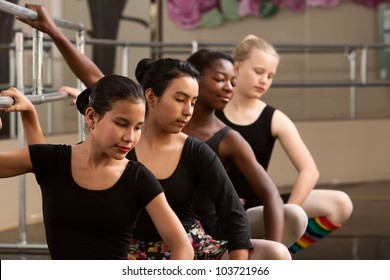 Group of four diverse ballet dancers warm up