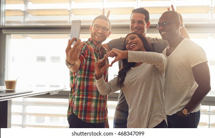 Group of four diverse silly employees taking self portrait and making symbolic hand gestures at small office in front of bright windows