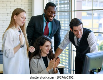 Group of four expertise multiracial businessmen and businesswomen managers clapping their hands with happiness to celebrate a successful company meeting with gathered in front of desktop computer