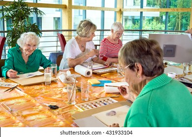 Group of four female cheerful older students painting together at table in spacious room with large windows