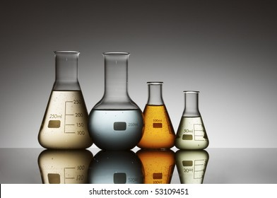 group of four flasks containing brightly colored liquid