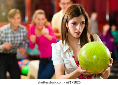 Group of four friends in a bowling alley having fun, three of them cheering the one girl in charge to throw the bowling ball