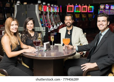 Group of four friends hanging out and having a few drinks together in a casino