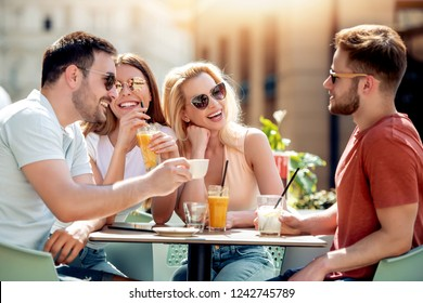 Group of four friends having fun at a coffee shop together. Two women and two men at cafe talking, laughing and enjoying their time.