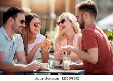 Group of four friends having fun and drink coffee together. Two women and two men at cafe talking ,laughing and enjoying their time