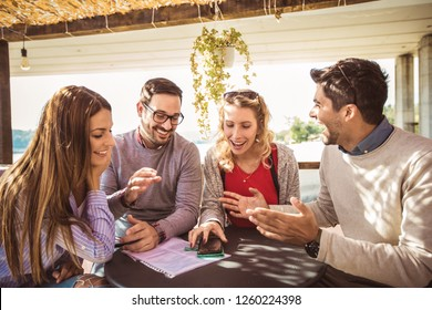 Group of four friends having fun a coffee together. Two women and two men at cafe talking laughing and using smart phone.