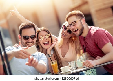 Group of four friends having fun in cafe together. Two women and two men at cafe talking, laughing and enjoying their time.